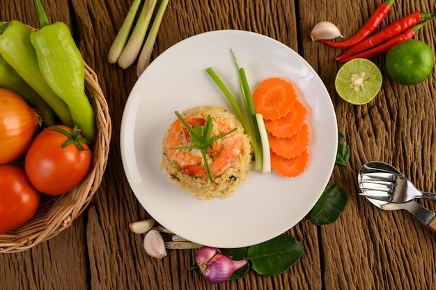 Riz Frit Aux Crevettes Sur Une Plaque Blanche Sur Une Table En Bois Photo gratuit