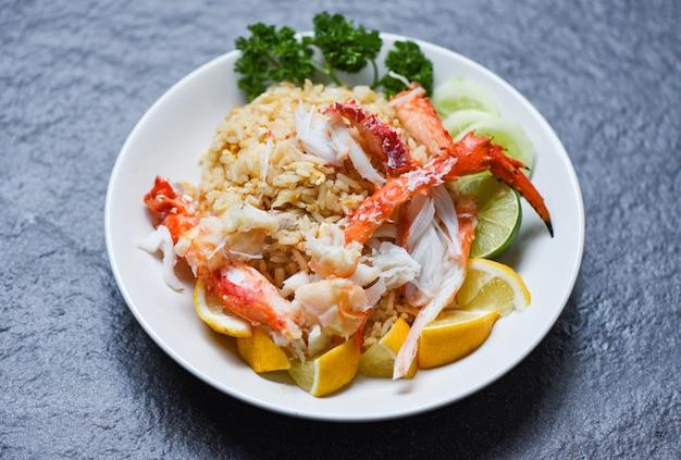 Riz frit aux fruits de mer - nourriture saine riz frit aux pattes de crabe avec citron et concombre sur une plaque blanche Photo Premium
