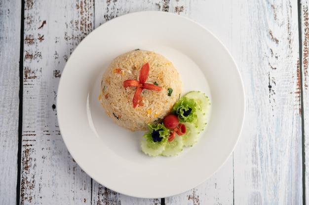 Riz Frit Aux œufs Dans Une Assiette Blanche Sur La Surface Du Bois Photo gratuit