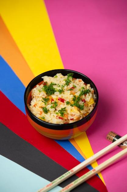 Riz Frit Aux Oeufs Avec Poivrons Et Aneth Sur Fond Coloré Photo gratuit