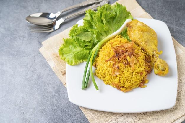 Riz jaune biryani de nourriture musulmane avec du poulet dans une assiette blanche sur le sol Photo Premium
