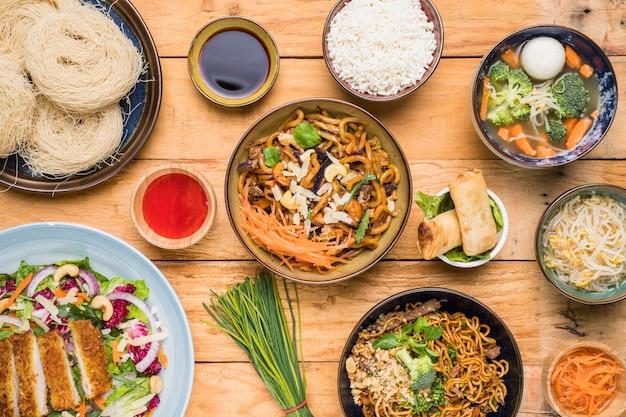 Riz; nouilles udon; rouleaux de printemps; ciboulette; haricots germés; soupe de boule de poisson et salade sur table Photo gratuit