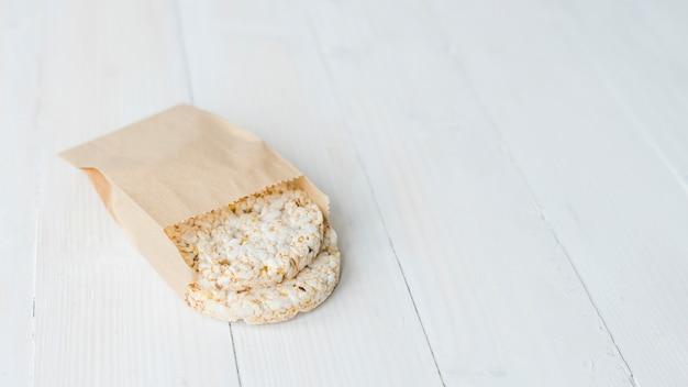 Riz soufflé croustillant fait maison dans un sac en papier brun sur un bureau en bois blanc Photo gratuit