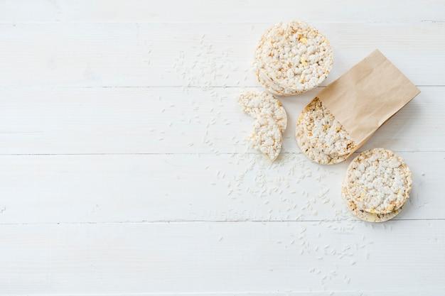 Riz soufflé fait maison avec des grains sur une planche blanche en bois Photo gratuit