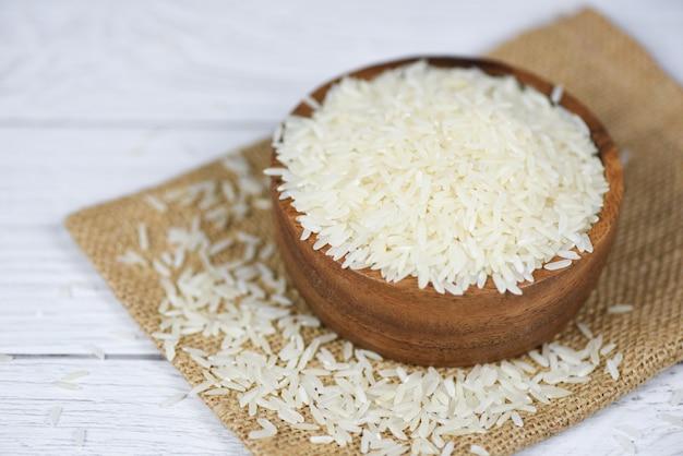 Riz Thaï Blanc Sur Bol Et Fond De Sac - Produits De Grain De Riz Au Jasmin Cru Pour L'alimentation En Asie Photo Premium
