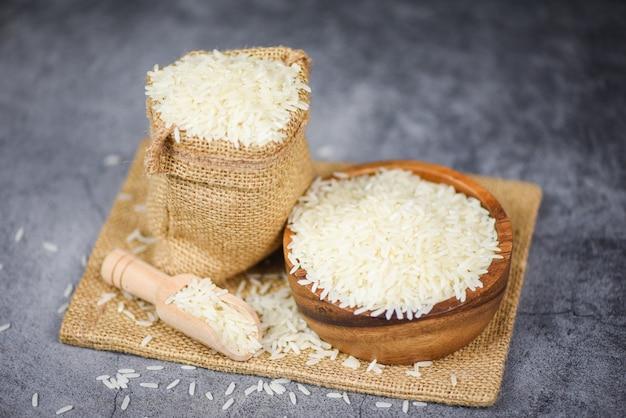 Riz Thaï Blanc Sur Bol Et Le Sac / Produits De Grain De Riz Au Jasmin Cru Pour L'alimentation En Asie Photo Premium