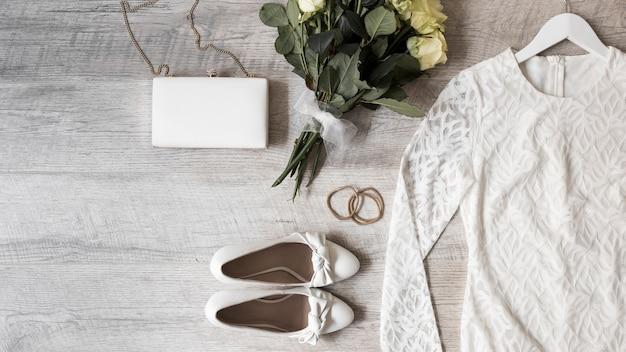 La robe de mariée; bouquet de fleurs; chaussures habillées; embrayage et élastiques sur fond en bois Photo gratuit