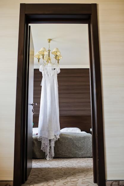 Robe de mariée élégante suspendue au lustre à l'intérieur de l'hôtel Photo Premium