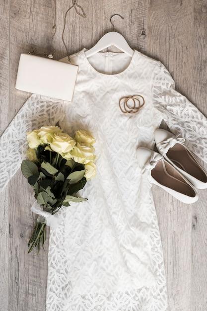 Robe de mariée avec embrayage de chaussures; bandeaux pour les cheveux et bouquet de roses attachées avec un ruban blanc sur fond en bois Photo gratuit