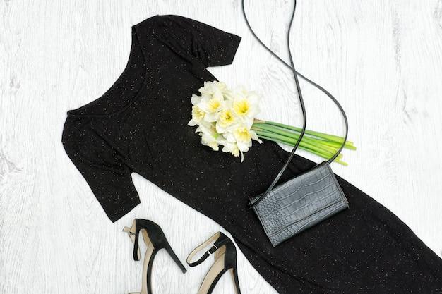 Robe noire, chaussures, pochette et un bouquet de jonquilles Photo Premium