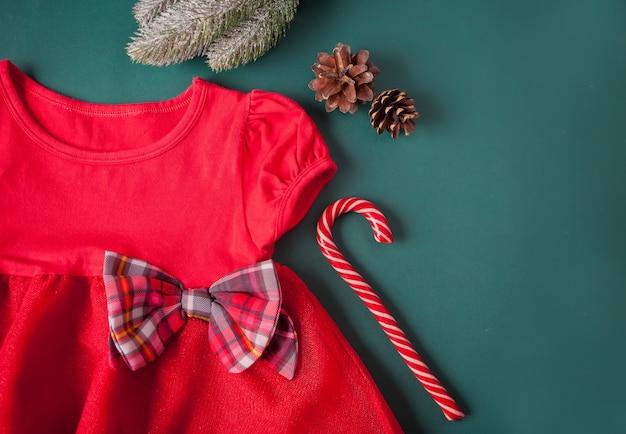 Robe Rouge Avec Noeud à Carreaux, Collants, Canne En Bonbon Sur Fond Vert Photo Premium