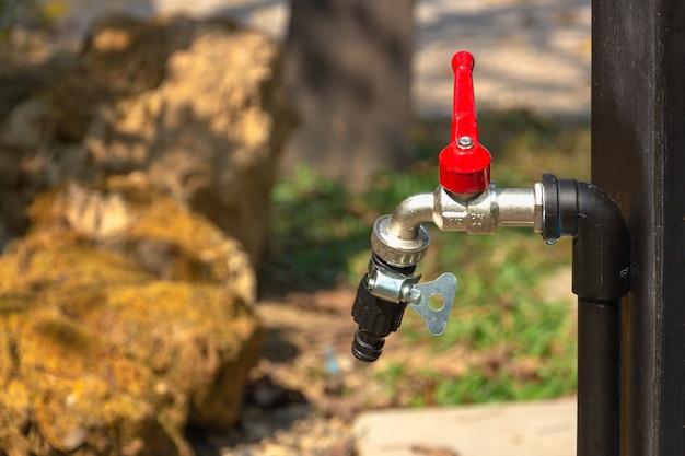 Robinet d'eau rouge dans le fond de la nature Photo Premium