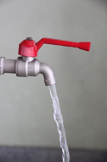 Le robinet est allumé et éteint l'eau. Photo Premium