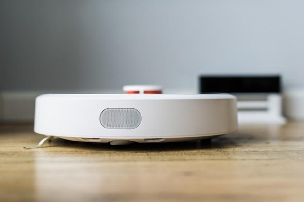 Robot aspirateur sur plancher en bois. vue de côté. concept de maison intelligente. nettoyage automatique. Photo Premium