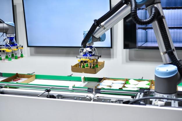 Un robot mécanique à intelligence artificielle trie les produits sur le convoyeur Photo Premium