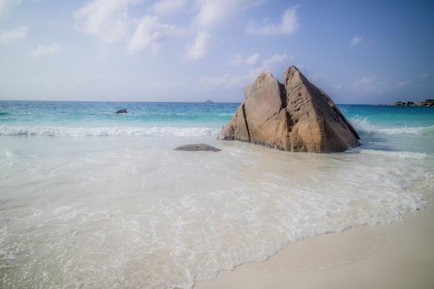 Roche Pointue Sur Une Plage Entourée Par La Mer Sous La Lumière Du Soleil à Anse Lazio à Praslin, Seychelles Photo gratuit