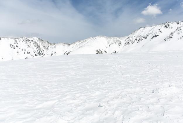 Rochers sur la neige couverte de montagne sous le ciel bleu Photo Premium