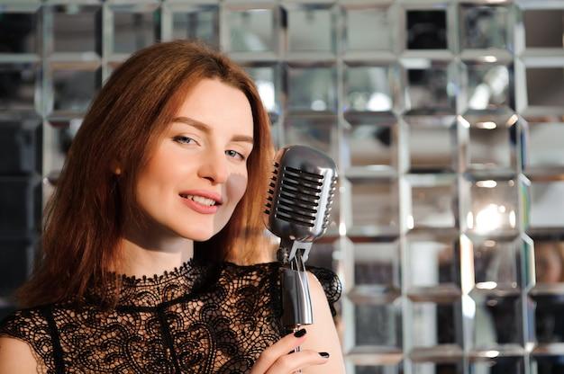 Rock star. fille sexy chantant dans un microphone rétro. Photo Premium