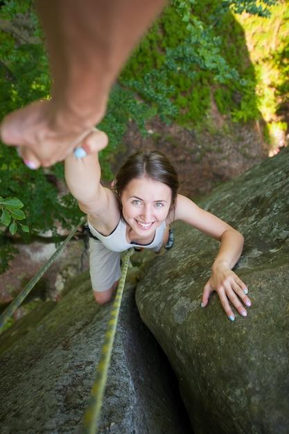 Rockclimber aide une alpiniste à atteindre le sommet de la montagne Photo Premium