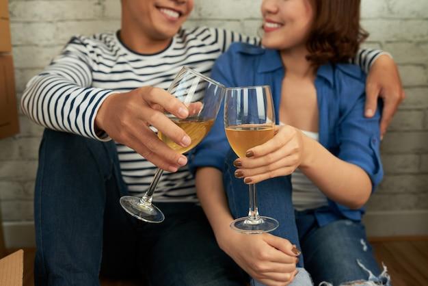 Rogné, couple, s'asseoir par terre, et, tinter, verres vin Photo gratuit