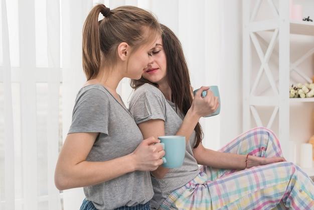 Romantique jeune couple de lesbiennes tenant la tasse de café à la main Photo gratuit