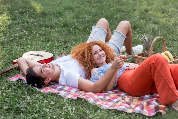 Romantique jeune couple pique-nique ensemble dans le parc Photo gratuit
