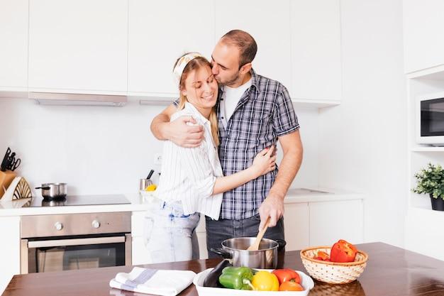 Romantique jeune couple prépare la nourriture dans la cuisine Photo gratuit