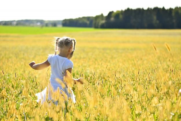 Romantique petite fille en robe blanche, marchant sur l'herbe dans le champ sur le coucher de soleil, regardant vers le bas, vue arrière Photo Premium