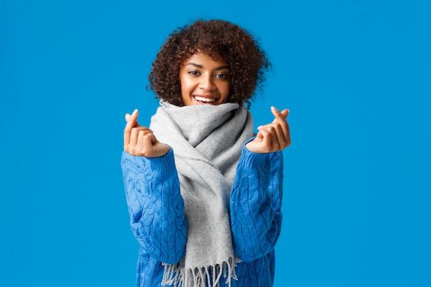 Romantique Et Stupide Petite Amie Afro-américaine Mignonne, Coupe De Cheveux Afro, Pull D'hiver Et écharpe, Attente Du Jour Et De La Date De La Saint-valentin, Montrant Les Signes Du Cœur Coréen Et Souriant, Bleu Photo Premium