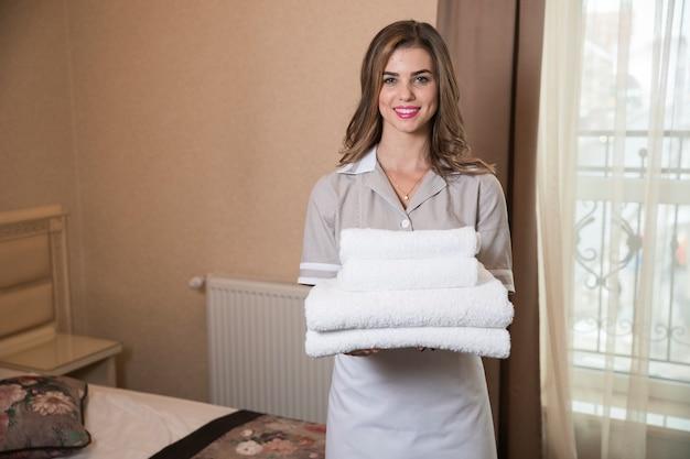 Room service maid tenant une pile de serviettes de bain blanches fraîches dans la chambre d'hôtel Photo gratuit