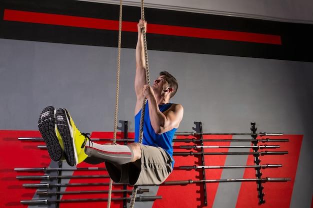 Rope climb exercice homme au gymnase Photo Premium