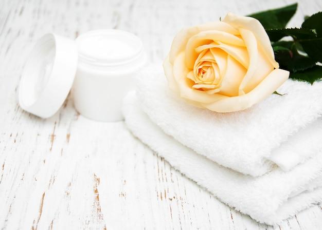 Rose avec crème hydratante et serviettes Photo Premium