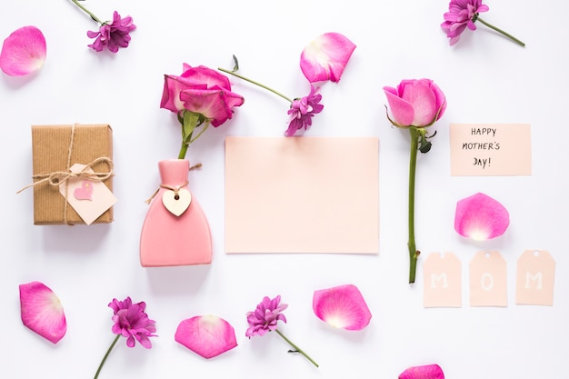 Rose dans un vase avec du papier et inscription heureuse fête des mères Photo gratuit