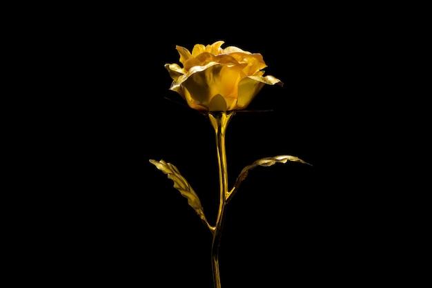 Rose d'or artificielle sur fond noir. Photo Premium