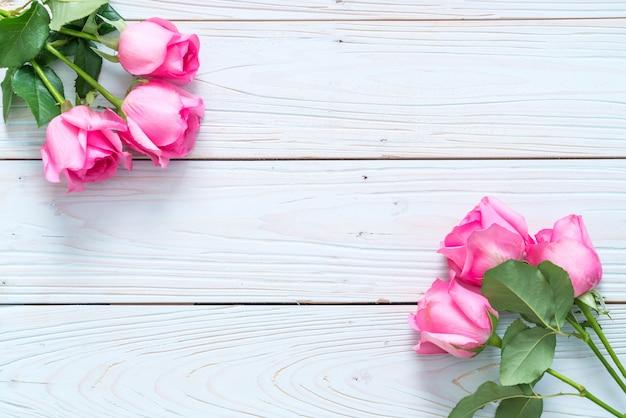 Rose rose dans un vase sur fond de bois Photo Premium