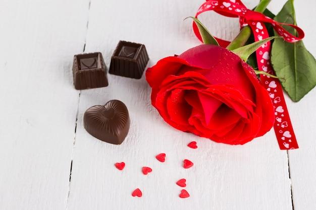 Rose Rouge, Chocolats Sur Fond De Bois Blanc Photo Premium