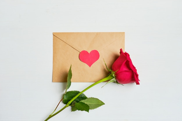 Rose Rouge Sur Une Enveloppe Avec Coeur Vue De Dessus. Photo Premium