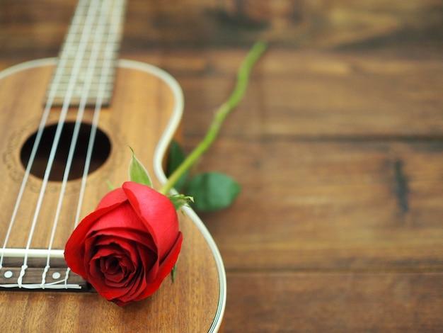 Rose Rouge Et Ukulélé Sur Un Fond En Bois Flou Pour La Carte De La Saint-valentin. Photo Premium