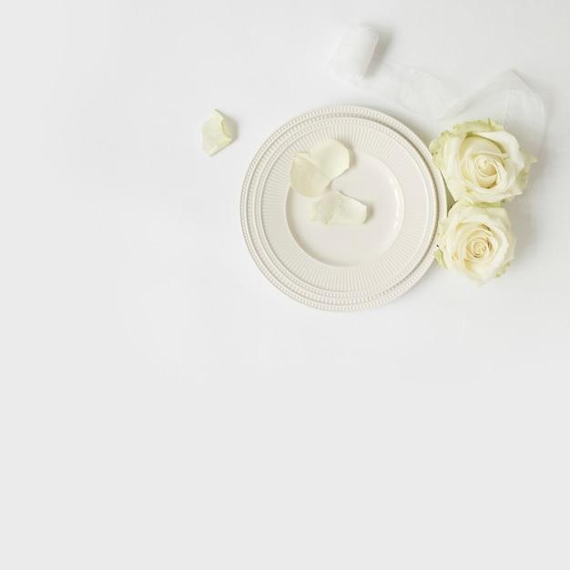 Rose; ruban blanc et assiettes sur fond blanc Photo gratuit