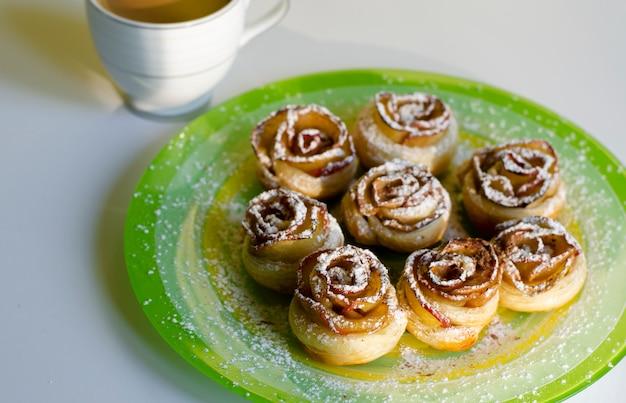 Roses De Biscuits Faits Maison Avec Une Poudre De Sucre Sur Une Assiette Colorée Et Une Tasse De Café Au Lait. Concept De Petit Déjeuner Et Dessert. Photo Premium