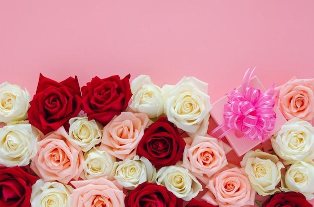 Roses Colorées Mises Sur Une Surface Rose Avec Une Boîte Cadeau Rose Pour La Saint-valentin Photo Premium
