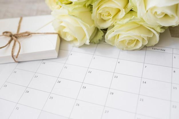 Roses jaunes et pile d'enveloppes sur calendrier Photo gratuit