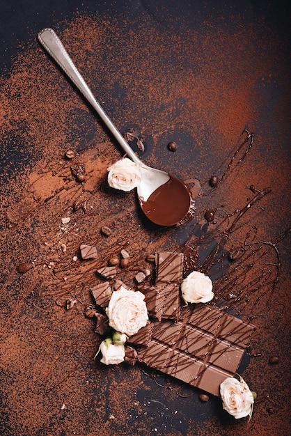 Roses Roses Avec Barre De Chocolat Et Sirop Sur Fond Texturé Foncé Photo gratuit