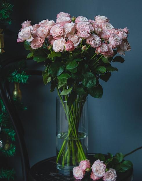 Roses roses dans un vase en verre avec de l'eau Photo gratuit