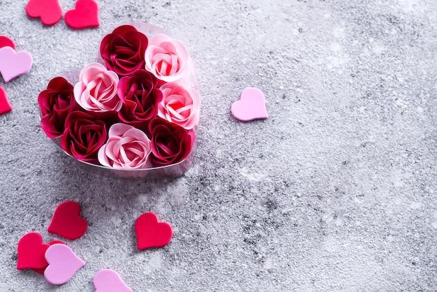 Roses roses et rouges vives faites de copeaux de savon avec des cœurs sur de la pierre, dans une boîte en forme de cœur. Photo Premium