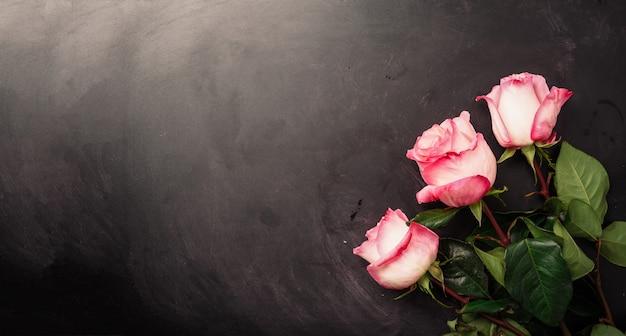 Roses roses sur un tableau noir. joyeuse journée de la femme. concept de la saint-valentin. cadeau pour elle Photo Premium
