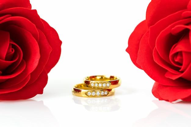 Roses rouges et bagues en or sur blanc Photo Premium