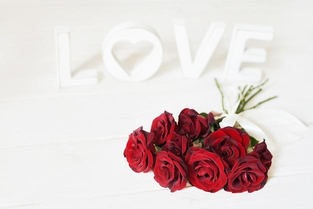 Roses rouges avec coeur, lettres d'amour en bois, modèle de carte postale Photo Premium