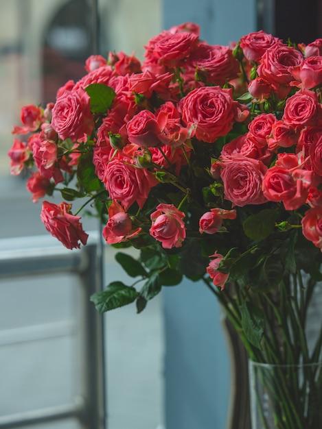 Roses rouges à l'intérieur d'un vase en verre transparent dans une pièce. Photo gratuit