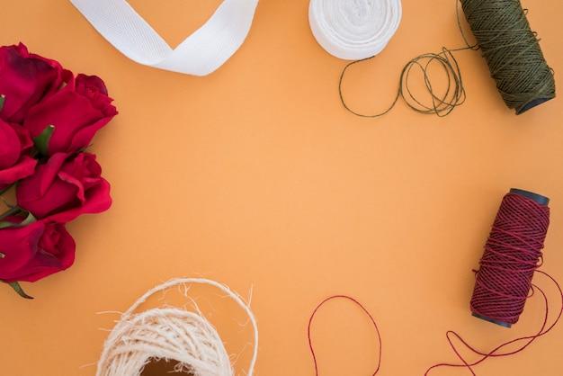 Roses rouges; ruban blanc; bobine de fil sur fond coloré Photo gratuit